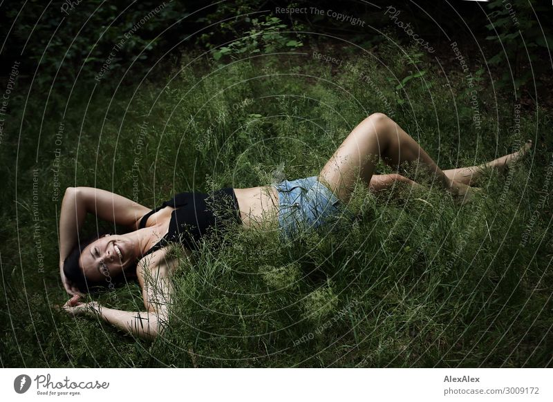 Portrait einer großen jungen Frau, die im Gras liegt und lächelt Lifestyle Freude Glück schön Leben Wohlgefühl Junge Frau Jugendliche 18-30 Jahre Erwachsene