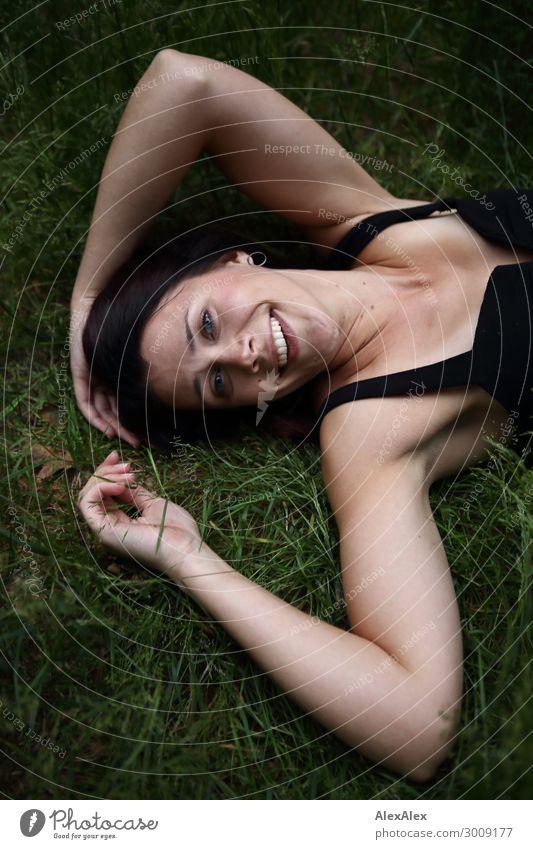 Junge Frau liegt in dunklem Wald im Gras Natur Jugendliche Pflanze schön Landschaft Erholung Freude 18-30 Jahre Gesicht Lifestyle Erwachsene natürlich lachen