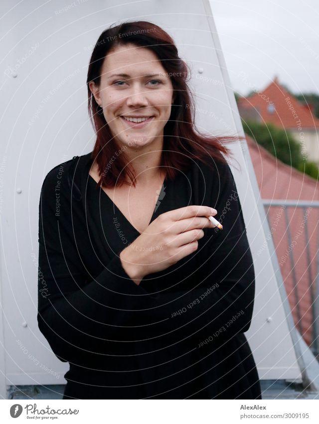 Portrait einer jungen Frau die auf ihrem Balkon steht und raucht Tabakwaren Lifestyle Freude schön Erholung Haus Junge Frau Jugendliche Grübchen 18-30 Jahre