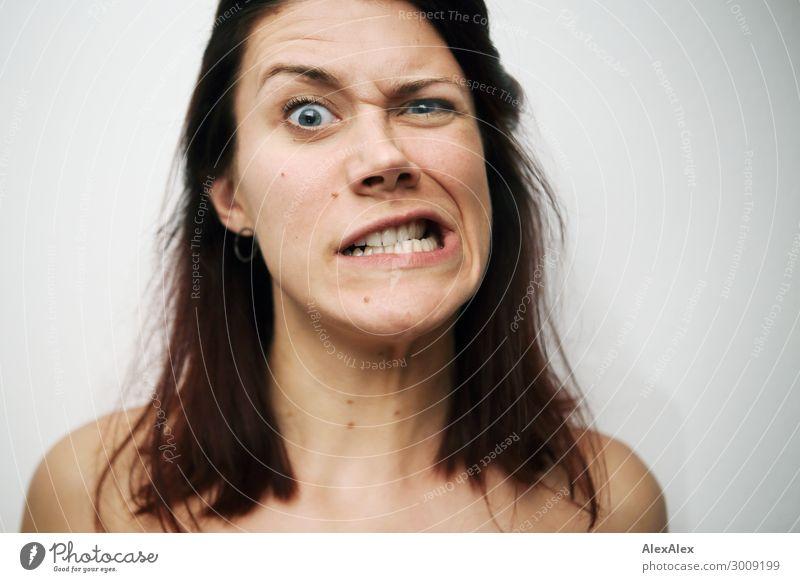 Portrait einer jungen Frau, die das Gesicht zu einer Fratze verzieht vor weißer Wand Lifestyle Freude schön Junge Frau Jugendliche 18-30 Jahre Erwachsene