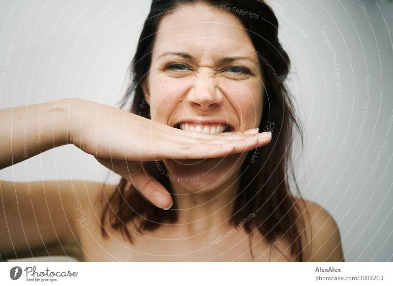 Nahes Portrait einer jungen Frau die sich in ihre Hand beißt vor weißer Wand Lifestyle Freude schön Leben Junge Frau Jugendliche Gesicht 18-30 Jahre Erwachsene