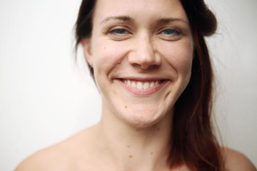 Sehr nahes Portrait einer lächelnden jungen Frau vor weißer Wand Lifestyle Freude Glück schön Leben Junge Frau Jugendliche Gesicht 18-30 Jahre Erwachsene