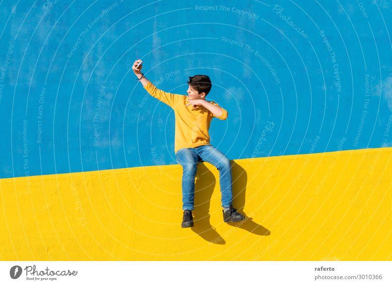 Vorderansicht eines Jungen in Freizeitkleidung, der auf einem gelben Zaun vor einer blauen Wand sitzt und ein Mobiltelefon benutzt Lifestyle Sommer Telefon