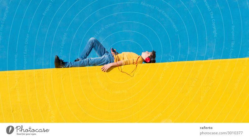 Kleiner Junge in Freizeitkleidung, der auf einem gelben Zaun liegt. Lifestyle Musik Telefon Handy PDA Technik & Technologie Mensch maskulin Kind Mann Erwachsene