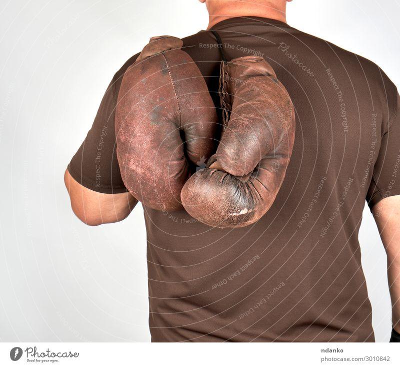 Athlet hält ein Paar sehr alte alte Boxhandschuhe. Lifestyle Körper Sport Sportler Erfolg Mann Erwachsene Hand Leder Handschuhe Fitness hängen braun Kraft