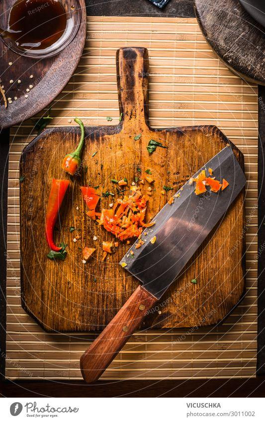 Gehackte Chilischote mit Messer auf Holzschneidebrett, Ansicht von oben. Scharfes Essen. Gewürze für schmackhaftes Kochen gehackt Peperoni Paprika hölzern
