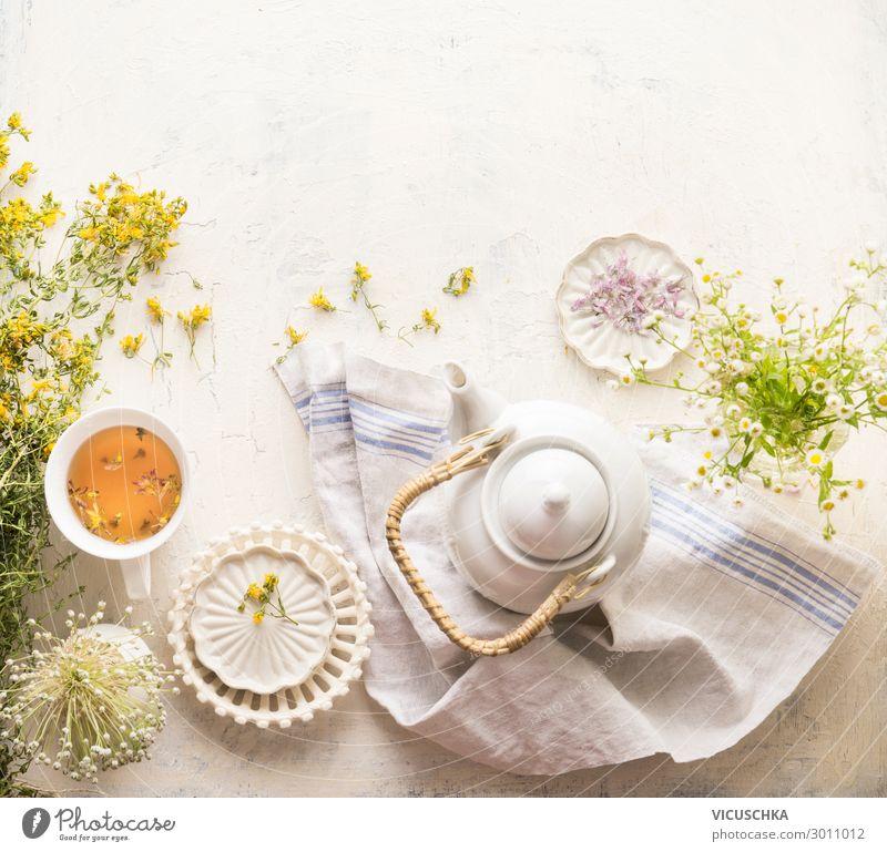 Kräuterteeset mit frischen Heilkräutern, Teekanne und Tasse Tee. Johanniskrautkräuter und Blumen auf weißem Tischhintergrund, Ansicht von oben. Kräutermedizin. Natürliches Nahrungsergänzungsmittel