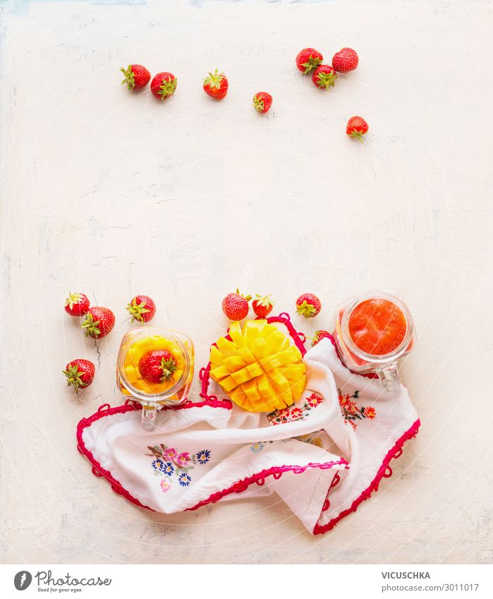 Gesunde Früchte und Beeren im Hintergrund des Frühstücks. Glasgläser mit Erdbeeren und Mangosmoothies auf weißem Tisch . Platz zum Kopieren Gesundheit Gläser