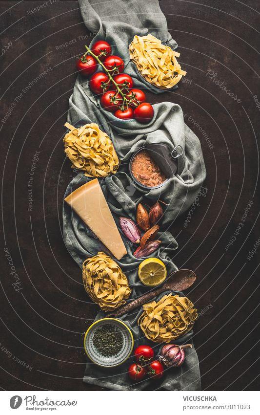 Thunfisch-Nudelkochzutaten auf dunklem, rustikalem Hintergrund, Ansicht von oben. Lebensmittelprodukte der italienischen Küche. Italienisches Essen. Kandierter Thunfisch. Vertikal. Flach liegend