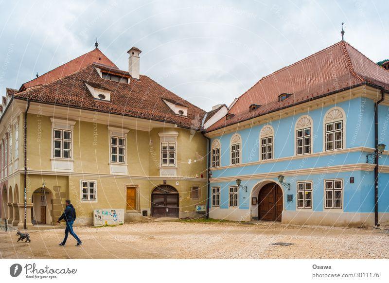 Mann mit Hund Stadt Haus Gebäude Ecke Platz Altbau Fenster Fassade Fußgänger Kopfsteinpflaster Textfreiraum oben Textfreiraum unten