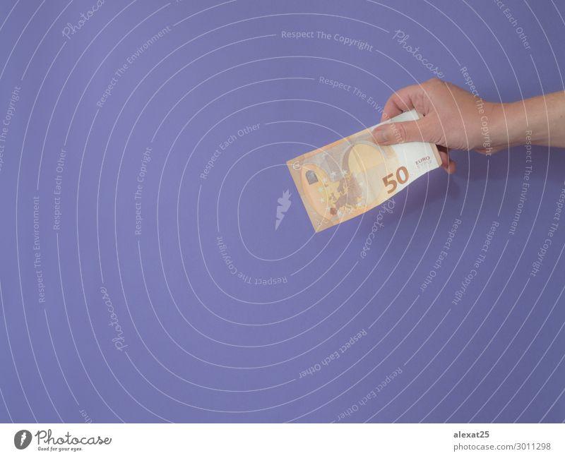 Hand mit Banknote von fünfzig Euro auf violettem Bankgrund mit Cop kaufen Geld Erfolg Kapitalwirtschaft Geldinstitut Business Mensch Frau Erwachsene Papier