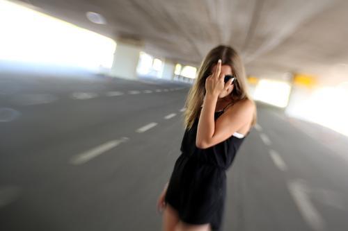 DramaQueen Lifestyle feminin Junge Frau Jugendliche 1 Mensch Brücke Straße Mode Kleid langhaarig frech gestikulieren Mittelfinger rebellisch Klischee