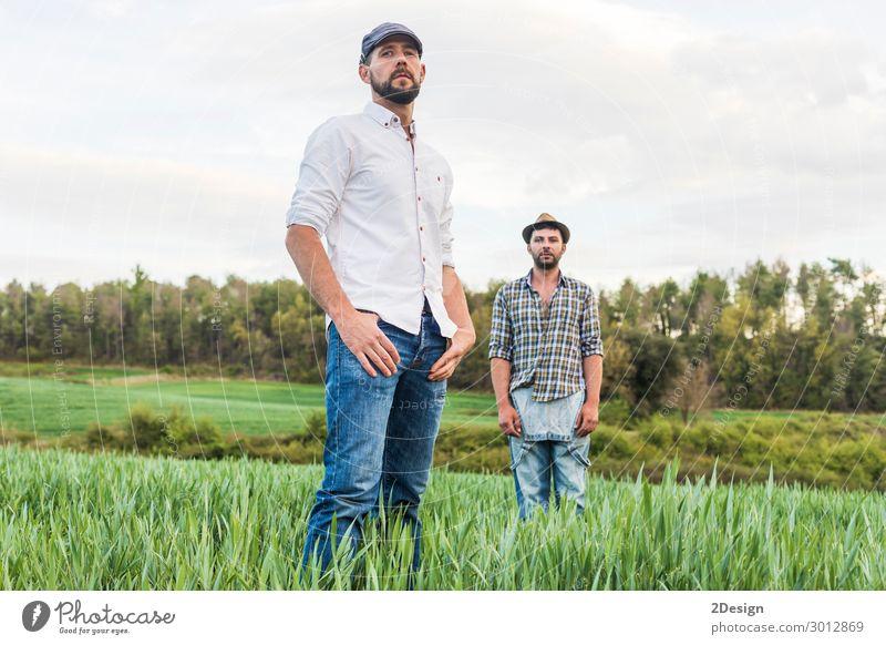 Zwei Männer stehen auf einem Haferfeld mit Wald im Hintergrund. Industrie Business sprechen Technik & Technologie Mensch maskulin Junger Mann Jugendliche