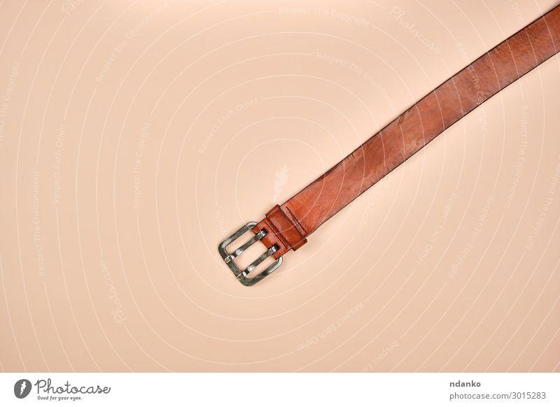 Fragment eines braunen Ledergürtels mit einer eisernen Schnalle elegant Stil Mode Bekleidung Stoff Accessoire Metall modern Aggression Gurt Hintergrund lässig