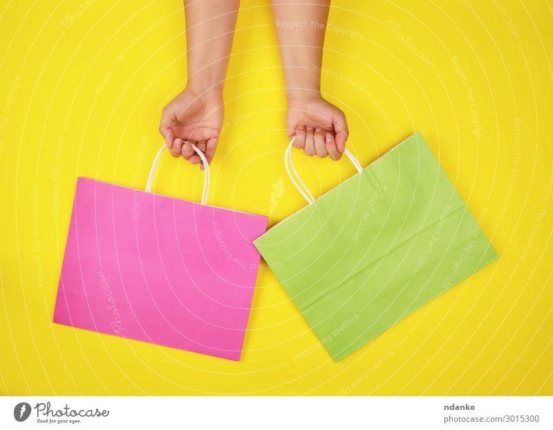 zwei Hände mit Papiertragetaschen Lifestyle kaufen Stil Design Business Hand Container Mode Verpackung Paket festhalten modern neu gelb grün rosa Farbe