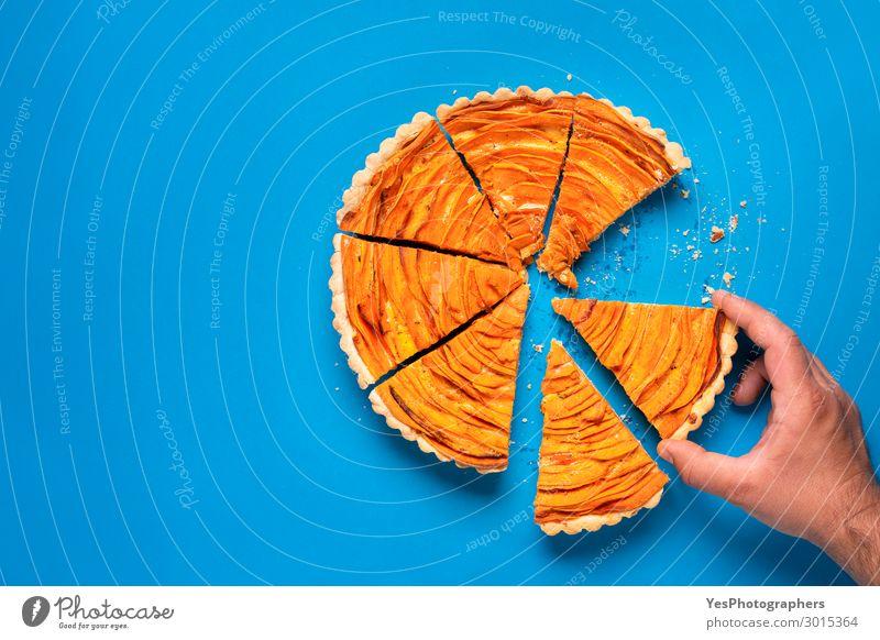 Mann Hand nimmt eine Scheibe Süßkartoffelkuchen. Essen Dekoration & Verzierung Herbst Tradition Erntedankfest obere Ansicht Amerikaner Blauer Hintergrund Krümel