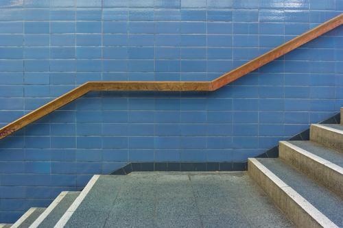 Treppenpodest Bauwerk Gebäude erschließen Geländer Treppengeländer Fliesen u. Kacheln Holz Stein Architektur abwärts aufwärts Bewegung Zentralperspektive