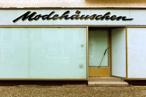 Modehäuschen Ladengeschäft Handel verkaufen Konsum Bekleidung Schaufenster geschlossen Blick Tür Eingangstür Zugang weiß Werbung außenwerbung Menschenleer