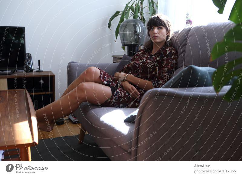 Junge Frau auf einer Couch im Wohnzimmer Jugendliche Stadt schön Erholung 18-30 Jahre Lifestyle Beine Erwachsene Innenarchitektur Stil Wohnung Zufriedenheit