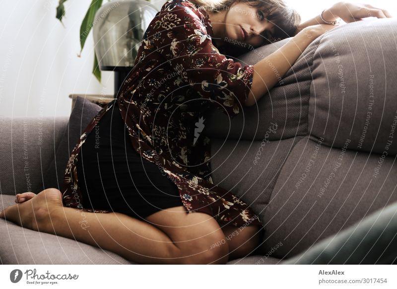 Junge Frau kniet auf einer Couch Lifestyle elegant Stil schön harmonisch Zufriedenheit Erholung Wohnung Sofa Wohnzimmer Jugendliche Beine 18-30 Jahre Erwachsene