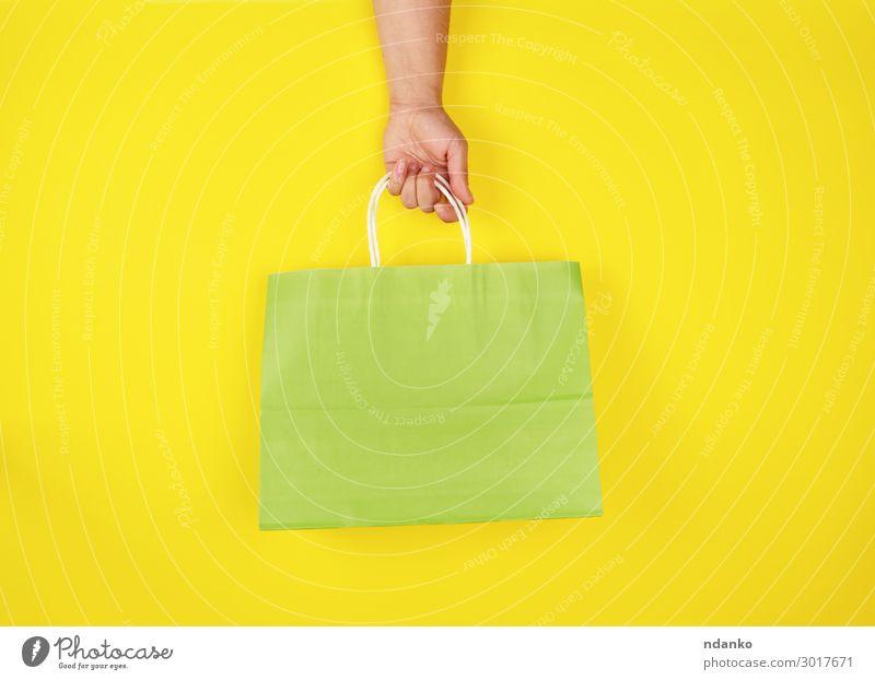 weibliche Hand mit einer grünen Papiertragetasche Lifestyle kaufen Stil Design Business Mensch Frau Erwachsene Container Mode Verpackung Paket modern neu gelb