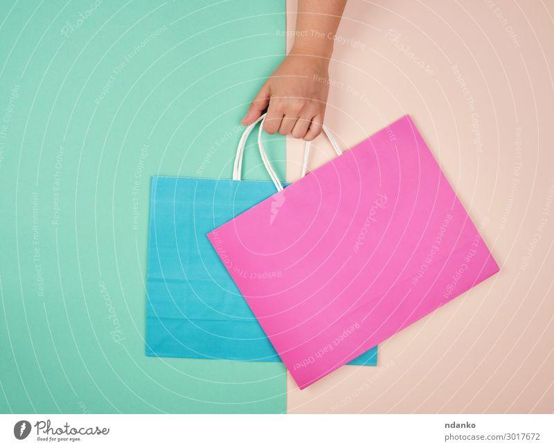 Hand hält zwei Papiertragetaschen Lifestyle kaufen Stil Design Business Frau Erwachsene Container Mode Verpackung Paket hängen modern neu grün rosa Farbe Idee