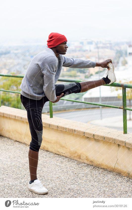 Schwarzer Mann, der sich dehnt, bevor er in der Stadt läuft. Lifestyle Körper Winter Sport Joggen Mensch maskulin Junger Mann Jugendliche Erwachsene Beine 1