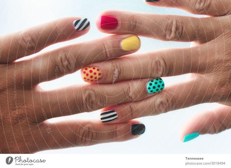 Ein Paar weibliche Hände mit farbig bemalten Nägeln. Fingernagel polnisch gemalt Farben und Lacke Muster mehrfarbig Design außergewöhnlich Behandlung Kunst Gel