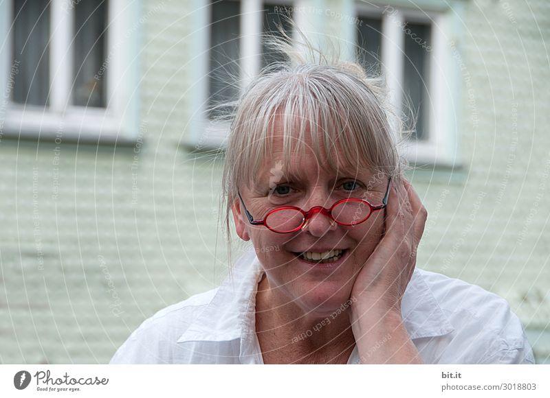 Reife Frau mit roter Brille auf der Nase, Ponyfrisur, grauen Haaren, steht vor weißem Haus mit Fenstern. Weiblicher Senior, mit Schmerzen an Ohr oder Zahn hält die Hand schützend an die Backe vom Gesicht. Dame mit erfreutem, überraschtem Gesichtsausdruck.