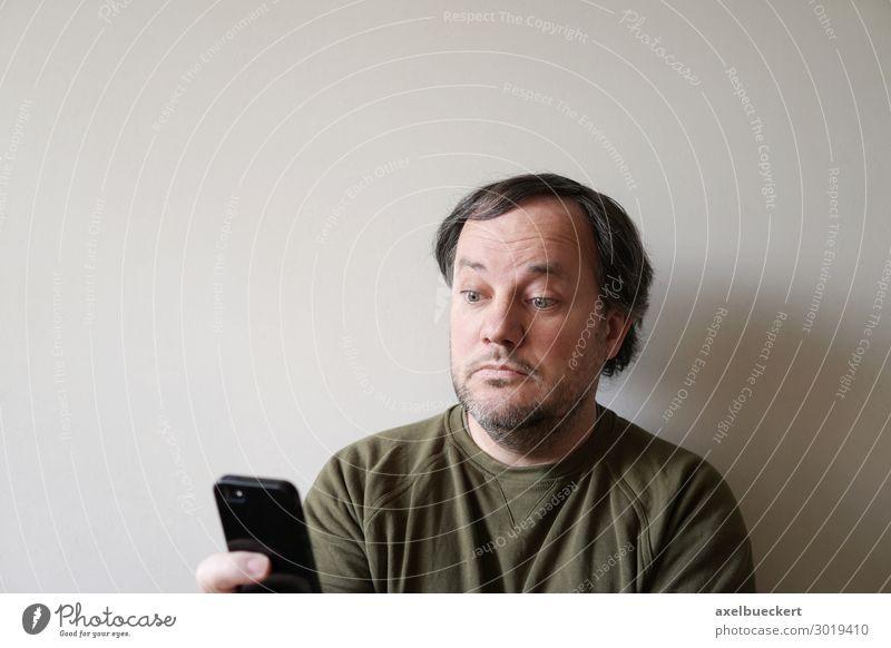 Mann schaut verdutzt auf Smartphone Lifestyle Telefon Handy PDA Technik & Technologie Unterhaltungselektronik Telekommunikation Internet Mensch Erwachsene 1