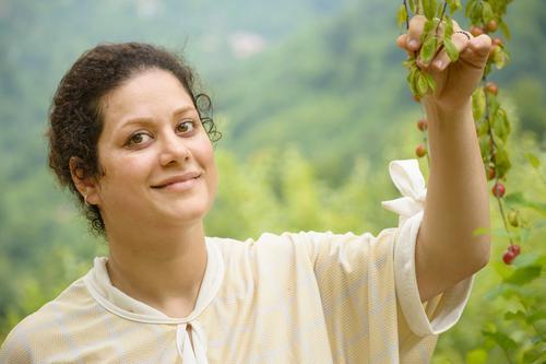 Porträt einer glücklichen jungen Frau mit Pflaumenästen Frucht Lifestyle Freude Glück schön Gesunde Ernährung Wohlgefühl ruhig Freizeit & Hobby Sommer Garten