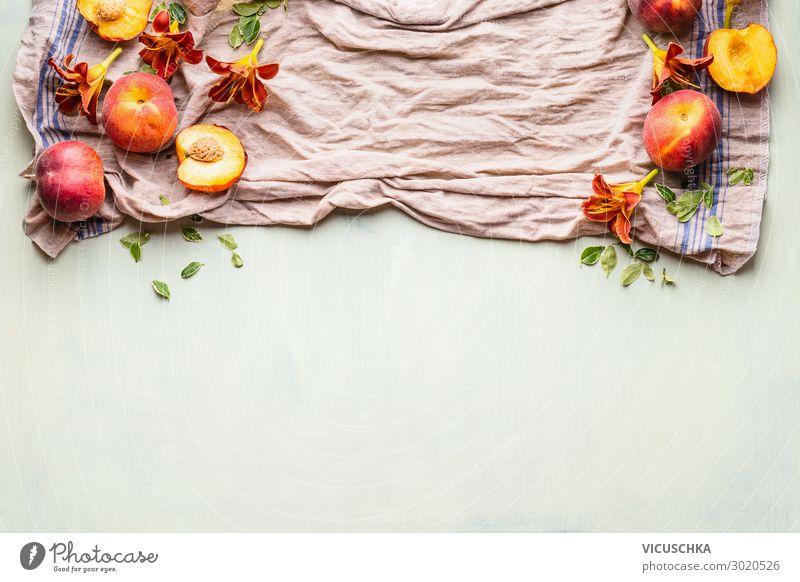Lebensmittelhintergrund mit frischen ganzen und halben Pfirsichen auf Küchentuch mit Blättern, Blumen und Kopierfläche für Ihr Design oder Produkt, Draufsicht. Flacher Schlag. Horizontal. Grenze