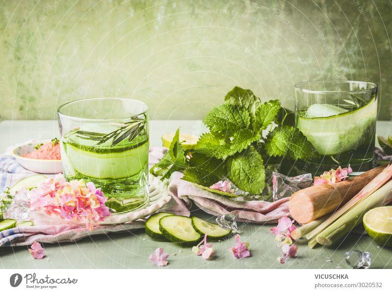 Klassen mit Gurkenlimonade oder Entgiftungswasser und Eiswürfel auf dem Tisch mit Zutaten. Grüne Farbe sommerliche Erfrischungsgetränke Zubereitung Salatgurke