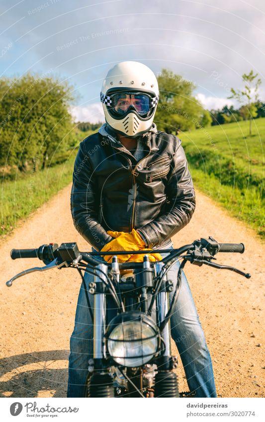 Mann mit Helm auf einem Custom-Motorrad Lifestyle Mensch Erwachsene Gras Verkehr Straße Wege & Pfade Fahrzeug Mode Jeanshose Handschuhe sitzen warten