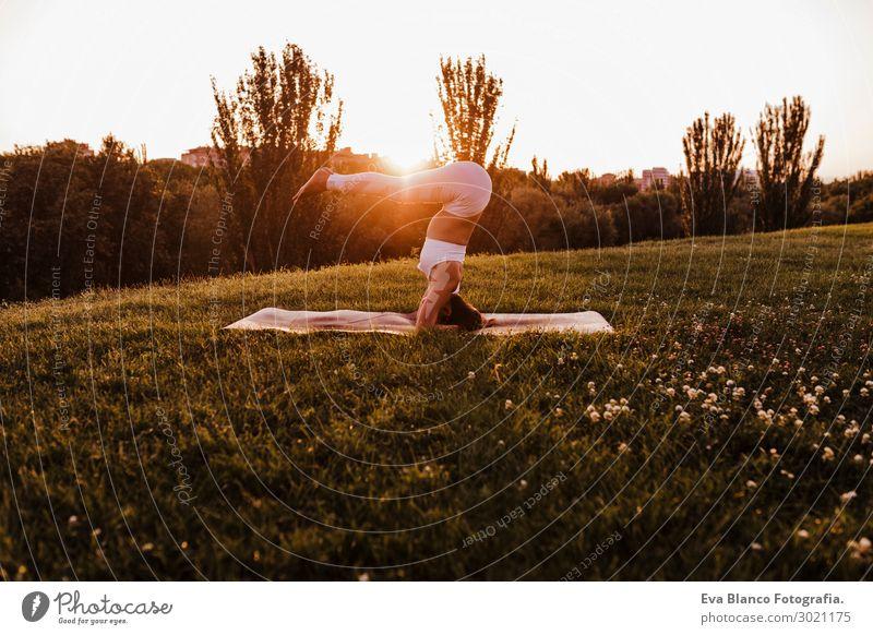 junge schöne asiatische Frau beim Yoga im Park bei Sonnenuntergang Lifestyle Glück Körper harmonisch Erholung Meditation Freizeit & Hobby Sommer Musik Sport