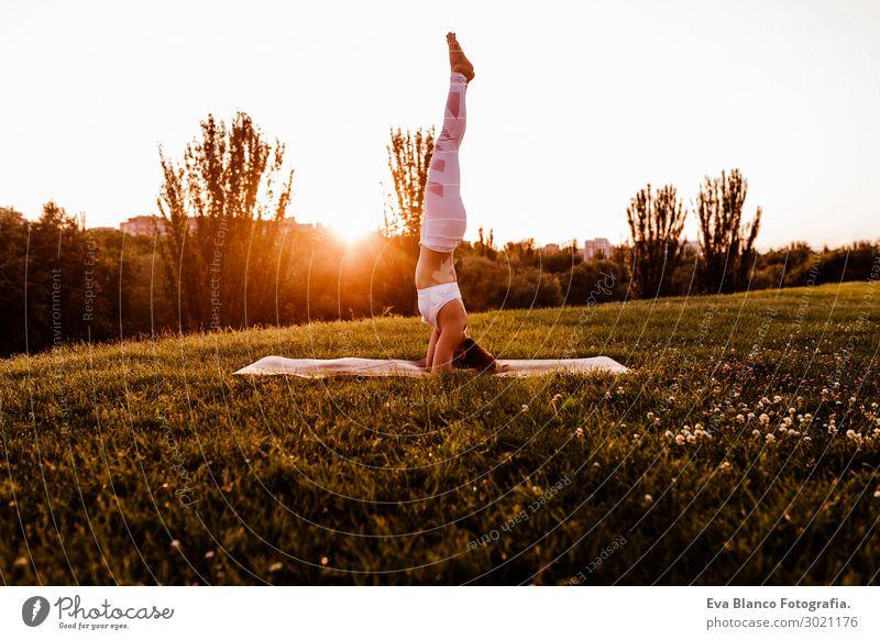 junge schöne asiatische Frau, die Yoga in einem Park bei Sonnenuntergang macht. Lifestyle Glück Körper harmonisch Erholung Meditation Sommer Musik Sport Mensch