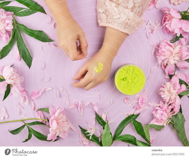 weibliche Hände und ein Glas mit dickem grünem Peeling Körper Haut Behandlung Wellness Spa Sommer Frau Erwachsene Hand Finger Pflanze Blume Blatt Mode