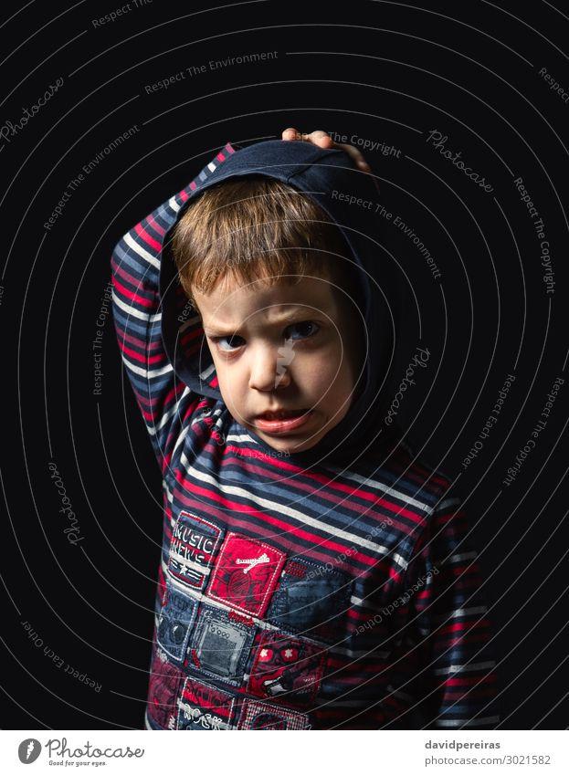 Wütender Junge mit Kapuzenpulli auf schwarzem Hintergrund Gesicht Kind Mensch Mann Erwachsene Kindheit stehen Traurigkeit authentisch dunkel klein niedlich