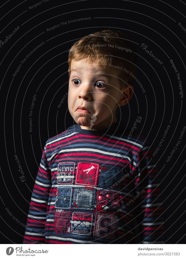 Verwirrter Junge mit Zweifelsgesicht über schwarzem Hintergrund Gesicht Kind Mensch Mann Erwachsene Kindheit Hemd Streifen Denken stehen authentisch dunkel