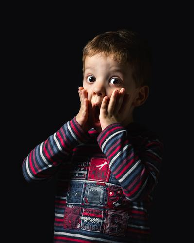 Überraschter Junge steht über schwarzem Hintergrund Freude Glück Gesicht Kind Mensch Mann Erwachsene Kindheit Mund Arme Hand Streifen stehen authentisch dunkel