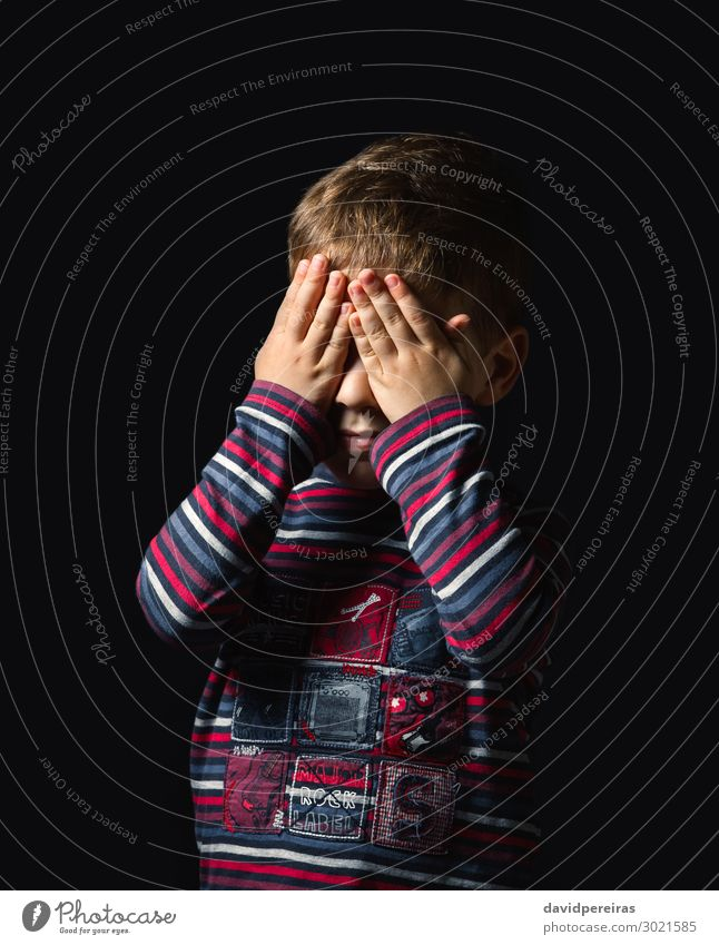 Ein ängstlicher Junge, der seine Augen vor schwarzem Hintergrund bedeckt. Gesicht Kind Mensch Mann Erwachsene Kindheit Hand Streifen stehen weinen authentisch
