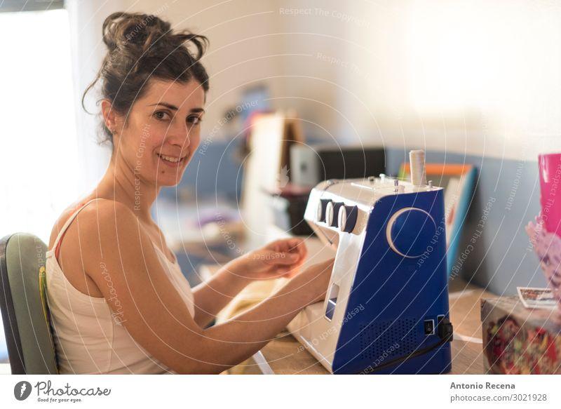 Hübsche brünette Frau, die zu Hause in der Maschine nähte, Arbeit & Erwerbstätigkeit Nähmaschine Mensch Erwachsene Bekleidung Stoff Lächeln dunkel Nähen Nadel