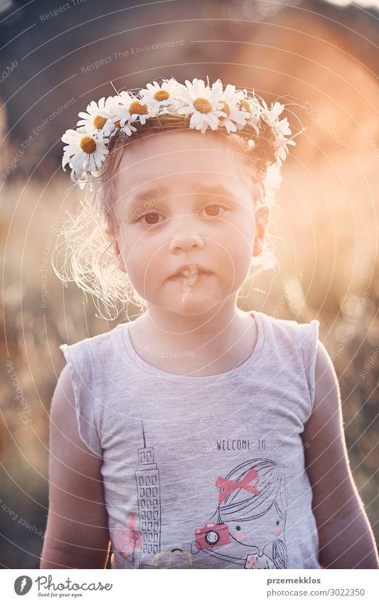 Kleines Mädchen trägt einen Krönchen aus Wildblumen auf dem Kopf. Lifestyle Freude Glück Erholung Freizeit & Hobby Spielen Ferien & Urlaub & Reisen Sommer Kind