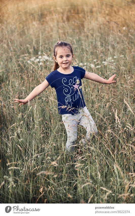 Kleines glückliches lächelndes Mädchen, das in einem hohen Gras spielt. Lifestyle Freude Glück Erholung Ferien & Urlaub & Reisen Sommer Kind Mensch 1 3-8 Jahre