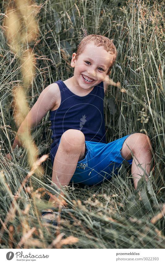 Kleine glückliche lächelnde Kinder, die in einem hohen Gras spielen. Lifestyle Freude Glück Erholung Ferien & Urlaub & Reisen Sommer Sommerurlaub Mensch Junge 1