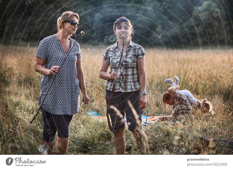 Frauen, die einen Marshmallow über einem Lagerfeuer braten. Lifestyle Freude Glück Erholung Freizeit & Hobby Spielen Ferien & Urlaub & Reisen Sommer