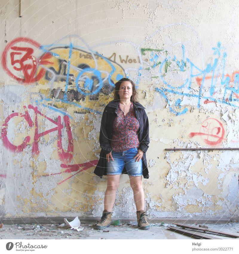 Porträt einer Frau mit kurzen Jeans, bunter Bluse und dunkler Jacke steht vor einer maroden Wand mit Graffiti Mensch feminin Erwachsene 1 45-60 Jahre Gebäude