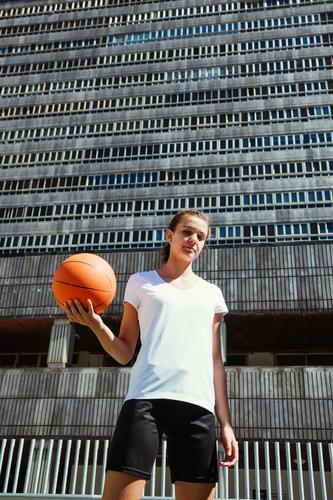 Junge Basketballspielerin auf einem städtischen Platz Lifestyle schön Spielen Sport Frau Erwachsene Jugendliche Park Hochhaus Straße hoch niedlich Mädchen