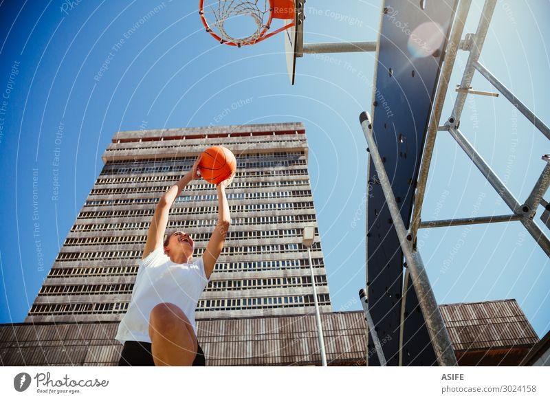 Mädchen spielt Basketball im Freien in der Stadt. Lifestyle Freude schön Spielen Sommer Sport Frau Erwachsene Jugendliche Himmel Park Hochhaus Gebäude Straße