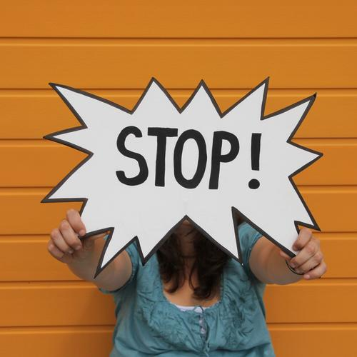 Warnschild Stop von einer Frau gehalten, vor einer orangen Wand Hand 1 Mensch 30-45 Jahre Erwachsene Fassade Bekleidung Hemd brünett langhaarig Schriftzeichen